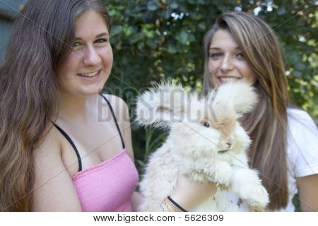 Two teenage girls holding a white Angora rabbit