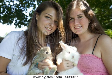 Two teenage girls holding baby rabbits