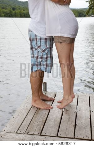Teenage couple hugging on a dock at a lake