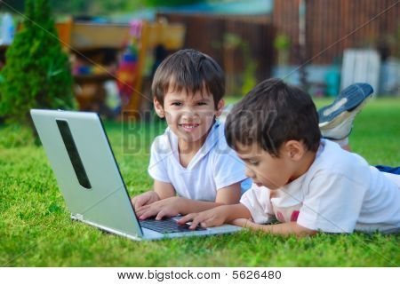 Two Cute Children Laying In Grass On Laptop