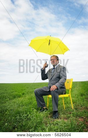 Senior business man with an umbrella