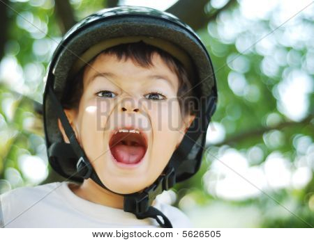Little Very Cute Kid With Helmet On Head And Funny Opened Mouth