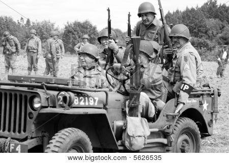 World War II re-enactors riding in a jeep