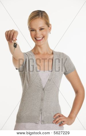 Young Woman Holding Out Keys Towards Camera