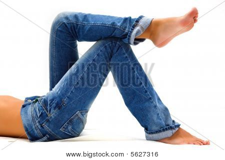 Girl's legs in a blue jeans over white