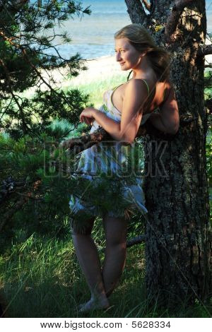 A Girl Leans Against A Tree
