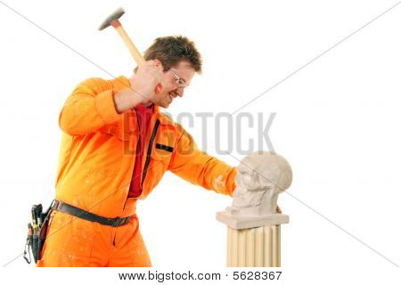Workman Beats A Stone Skull With A Hammer