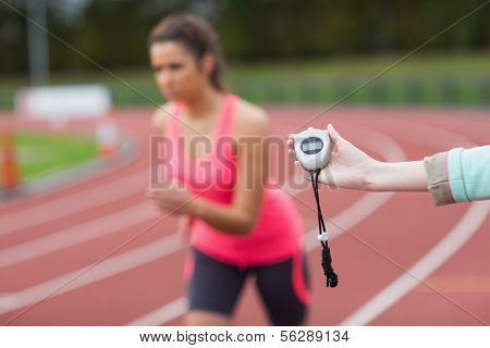 Close-up of a hand timing a blurred young woman's run on the running track