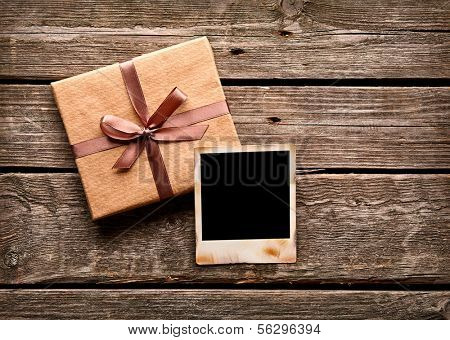 Blank photo frame with gift box on old wooden background.