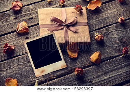 Blank photo frame with gift box, petals and rose flowers on old wooden background.