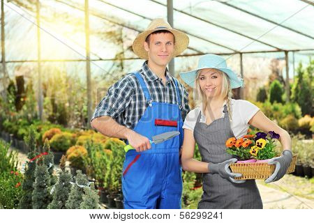 Male and female gardeners with basket full of flowers and small shovel posing in hothouse