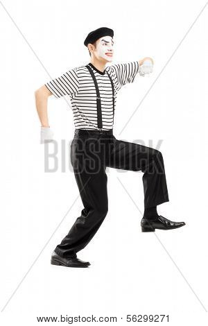 Full length portrait of male mime artist simulate walking on rope, isolated on white background
