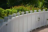 stock photo of virginia  - White picket fence with green grass background and lowers in background - JPG
