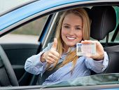 Attractive young woman proudly showing her drivers license.