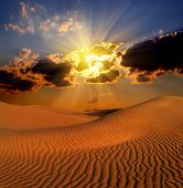 stock photo of arid  - dramatic cloudy suset landscape in desert - JPG