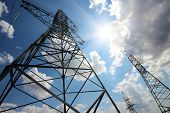 stock photo of mast  - tall electric masts against sun and cloudy sky - JPG