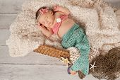 stock photo of mermaid  - Newborn baby girl wearing a crocheted teal and coral colored mermaid costume - JPG