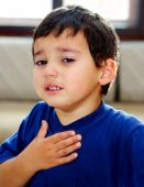 stock photo of fussy  - Crying emotional kid with tears on his cheeks and hand on the chest - JPG