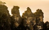 picture of three sisters  - Rising sun illuminates the Three Sisters rock formation in the valley from Echo Point overlooking the majestic Blue Mountains near Sydney NSW Australia - JPG