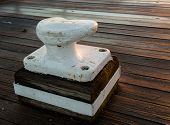 pic of bollard  - Setting sun shines warm light on a white painted ships bollard for securing a boat - JPG