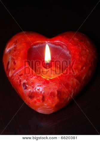 Lit red heart candle, dark background