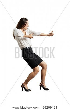 screaming businesswoman pulling invisible rope. isolated on white background
