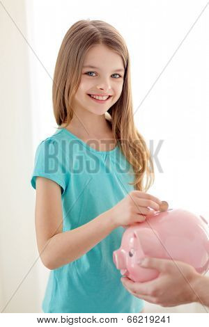 education, family, child and money saving concept - father holding piggy bank and child putting coins into it