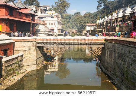 KATHMANDU, NEPAL - DEC 3, 2013: During the cremation ceremony along the holy Bagmati River in Bhasmeshvar Ghat at Pashupatinath temple in Kathmandu.