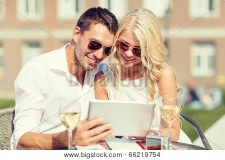 summer holidays, dating and technology concept - couple looking at tablet pc in cafe in the city