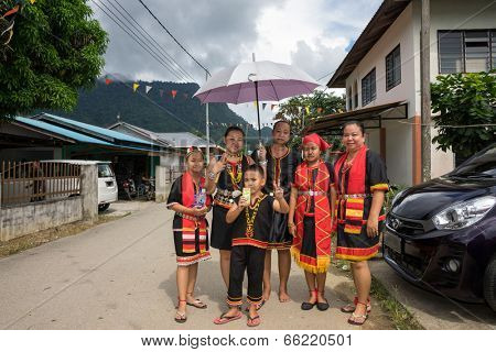 SARAWAK, MALAYSIA: JUNE 1, 2014: A family wearing traditional Bidayuh costumes wait for the parade to pass through their house, in a procession celebrating thanksgiving day, called the Gawai festival.
