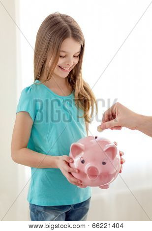 education, family, child and money saving concept - smiling little girl holding piggy bank and father putting coin into it