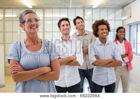 Business team standing with arms folded in the office