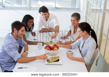 Business people eating sandwiches and fruit for lunch in the office