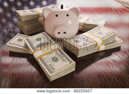 Thousands of Dollars and Piggy Bank with Reflection of American Flag on Table.