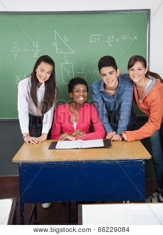 Portrait of African American teacher with teenage students at desk in classroom