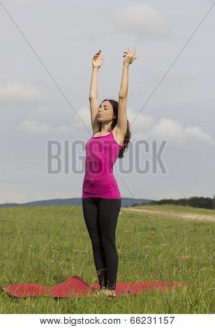 Woman Doing Sun Salutation In Yoga Outdoors
