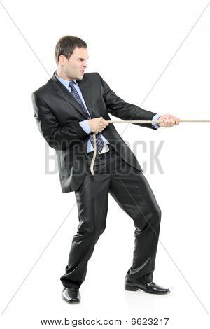 A young businessman pulling a rope