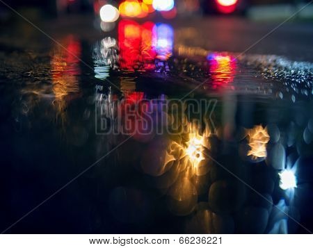 Colorful traffic lights bokeh circles reflecting in water on night city street. Abstract background.