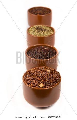 four tea cups full with tea