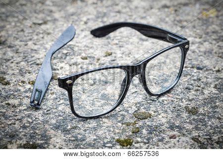 Broken black glasses fallen on tarmac