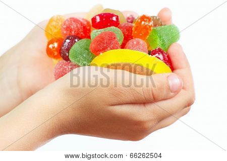 Child hands with colorful candies and sweets close up