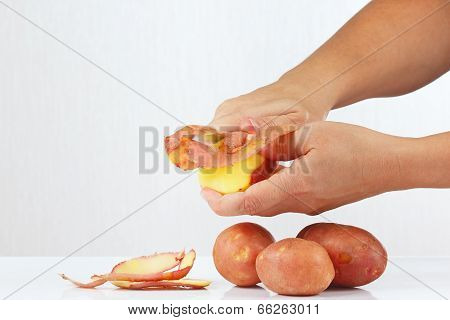 Hands peeling potatoes with a knife