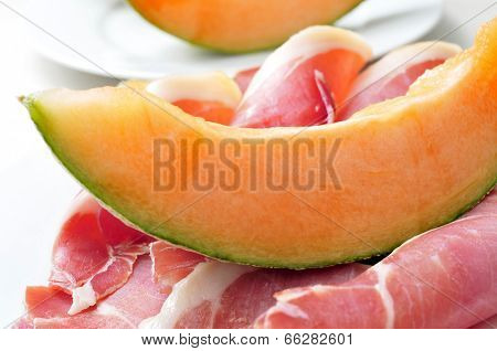 closeup of a plate with melon and spanish jamon serrano, to prepare melon con jamon, a typical summer dish in Spain