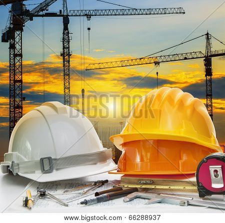 Civil Engineer Working Table With Safety Helmet And Writing Instrument Against Beautiful Dusky Sky A