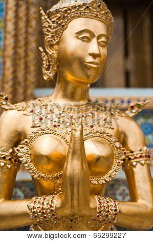 Golden Kinnari Statue At Temple Of Emerald Buddha In Grand Royal Palace. Bangkok, Thailand