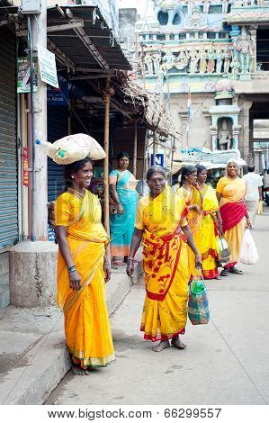 Indian Woman In Colorful Sari Carrying Bale On Head At Crowded Street