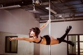 stock photo of pole dancer  - young pretty girl pole dancing in a dance hall - JPG