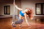 stock photo of pole dance  - young pretty girl pole dancing in a dance hall - JPG