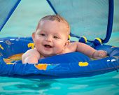stock photo of canopy  - Happy infant playing in pool while sitting in baby float with canopy - JPG