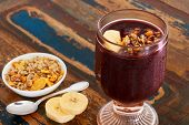 stock photo of brazilian food  - Acai juice in glass with muesli banana spoon on wooden table - JPG